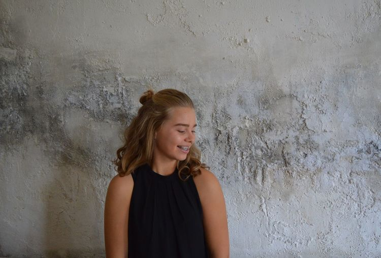 Happy teenage girl standing against weathered wall