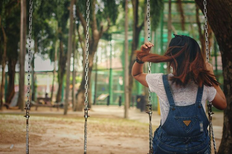 Rear view of woman sitting on swing in playground