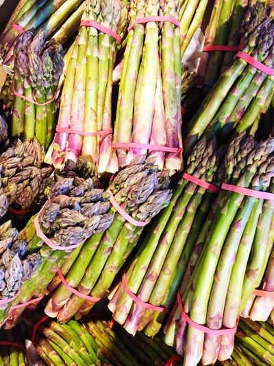 A full frame background of bunches of freshly picked, organic asparagus tips on a market stall