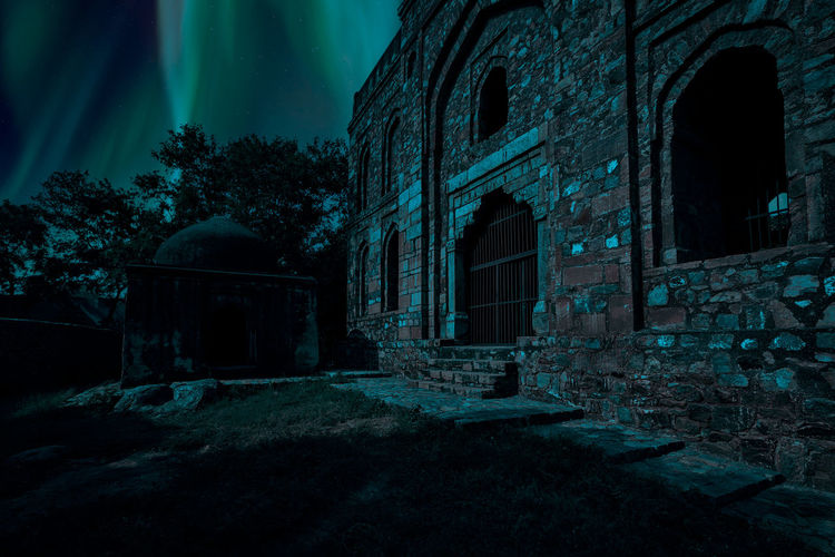 Old ruin building against sky at night
