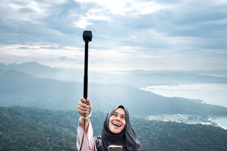 Young Woman Holding Monopod On Against Mountains