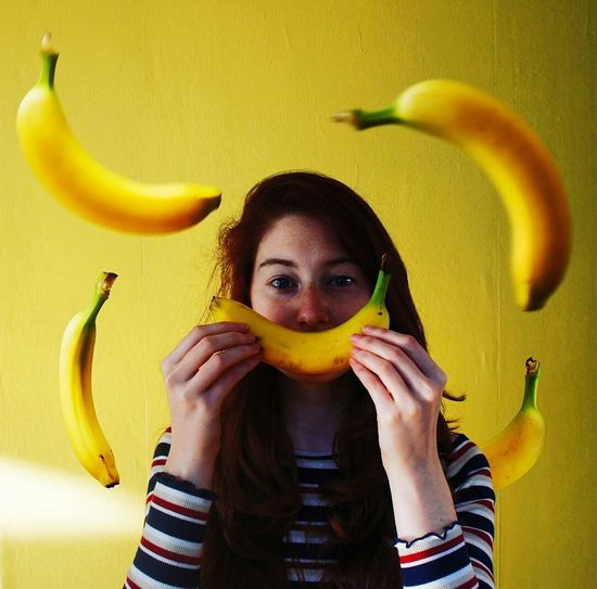 Portrait of beautiful young woman with bananas