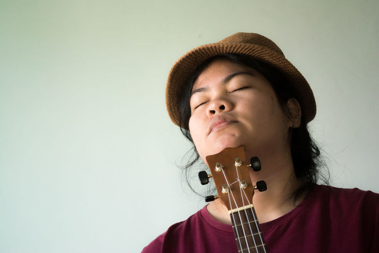 Eyes closed woman with ukulele wearing hat against gray background