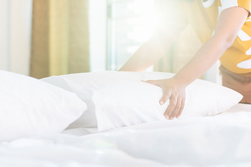 Midsection of man sitting on bed