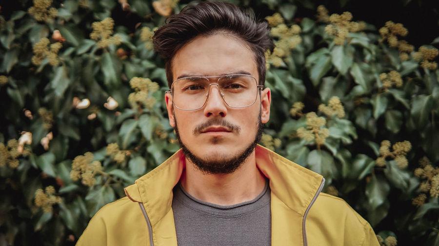 Portrait of young man against plants