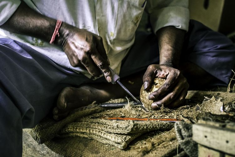 Midsection Of Man Cutting Coconut On Burlap