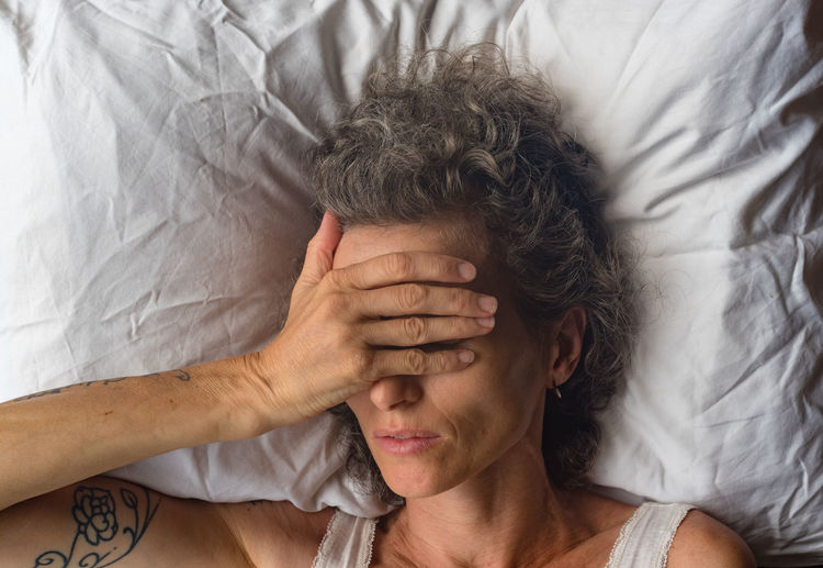 Directly Above Shot Of Woman With Head In Hand Sleeping On Bed At Home