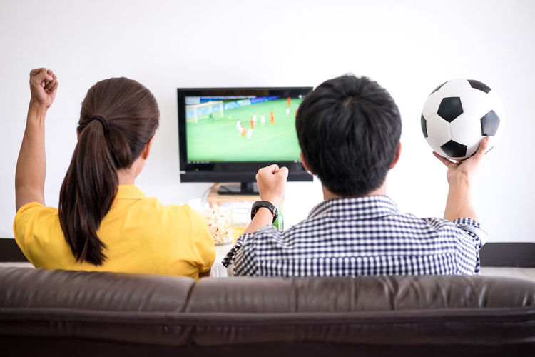Rear View Of Men And Women Watching Match On Sofa At Home