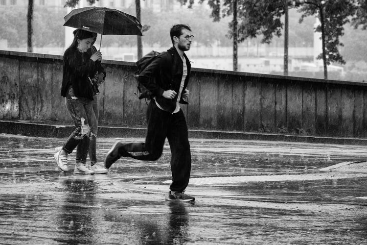 Full length of man with wet umbrella in city during monsoon