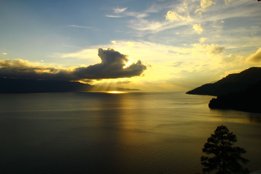 Sunset behind the cloud with ray of light in the Toba Lake, North Sumatera. Ray Of Light Ray Of Sun Ray Of Light! Ray Of Sunlight Sunset Lovers Photography By @jgawibowo Shot By Arif Wibowo Travel Photography Travel Travel Destinations INDONESIA Scenic View Scenic Photograghy Likeforlike Like4like Photography Eyeem Landscape Official Photo Club📷 EyeEm Landscape EyeEm Nature Lover Sea Sunset Cloud - Sky Nature Sky Outdoors Beach Silhouette Landscape Beauty In Nature Scenics