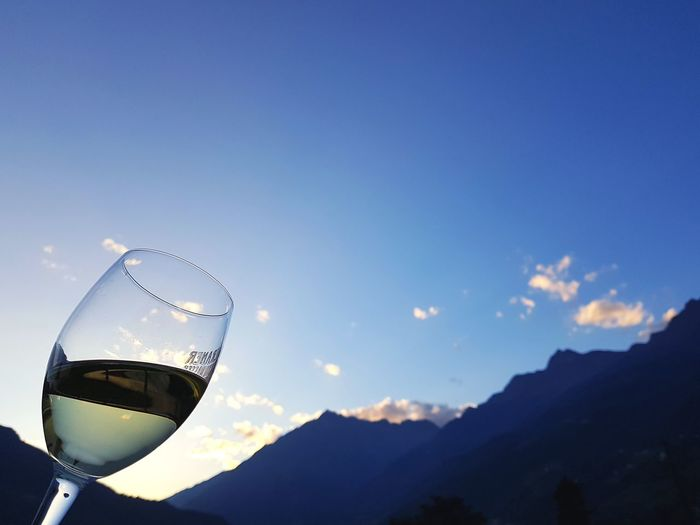 Low angle view of wine glass against mountains at sunset
