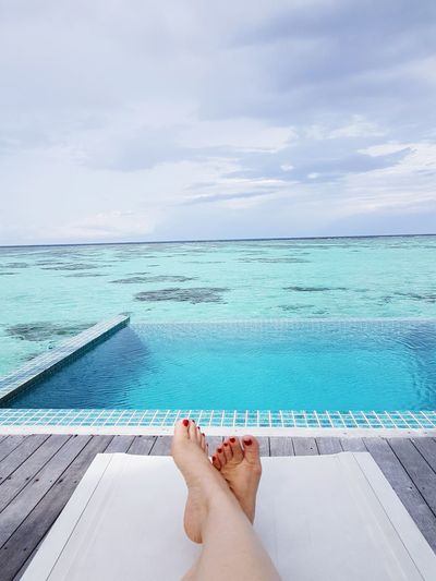 Low section of woman relaxing by infinity pool against sky