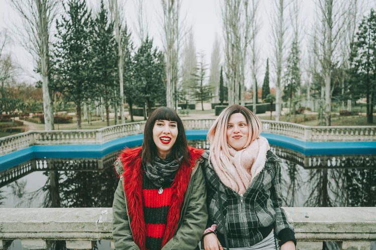 Portrait of smiling friends leaning on railing against lake during winter