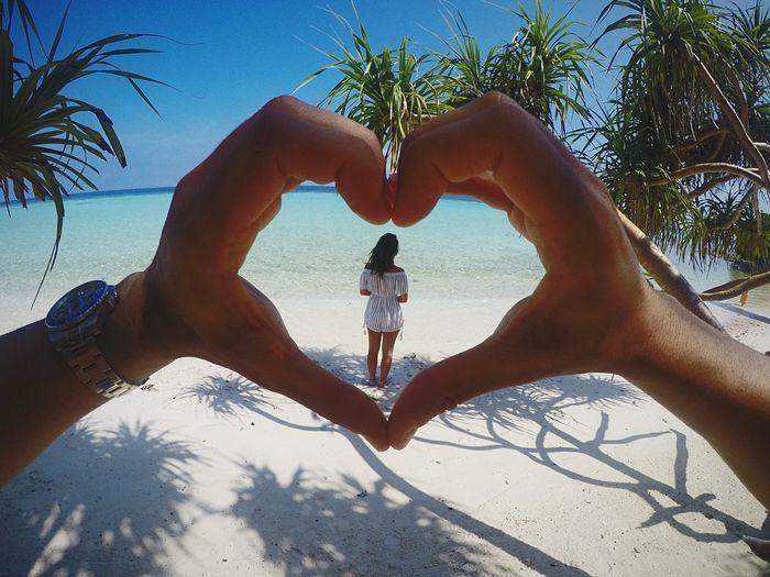 Woman seen through hands of man making heart shape standing at shore of beach
