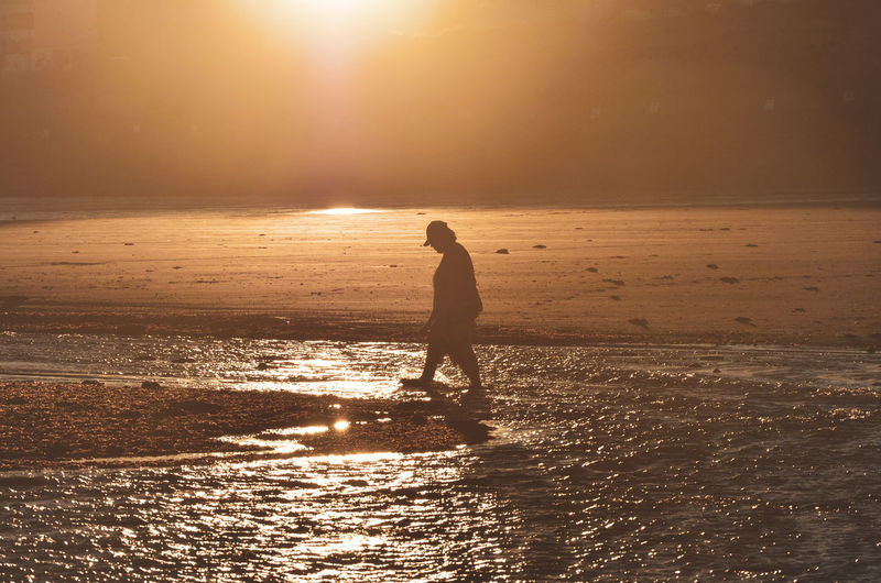 Beach Beauty In Nature Full Length Horizon Horizon Over Water Land Leisure Activity Lens Flare Lifestyles Nature One Person Outdoors Real People Scenics - Nature Sea Silhouette Sky Sun Sunlight Sunset Water