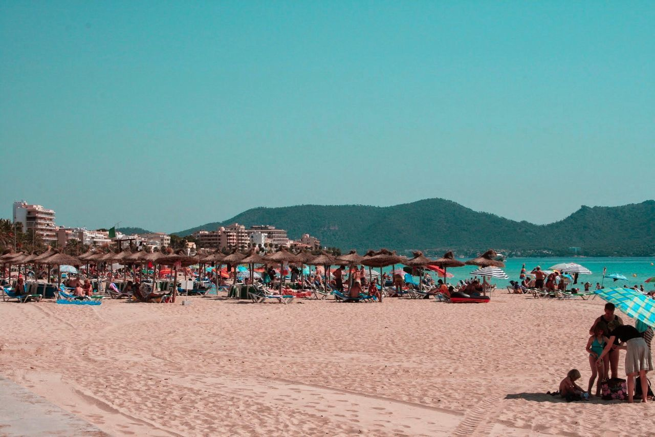 sand, large group of people, beach, vacations, summer, outdoors, clear sky, travel destinations, day, blue, sea, people, desert, adults only, adult, crowd, nature, sky, only men