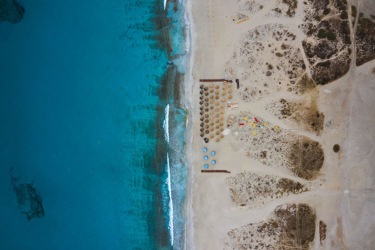A small umbrella set up lays along a secluded beach in Naxos, Greece. Naxos Aquatic Sport Beach Beachphotography Beauty In Nature Blue Day Dji Greece High Angle View Land Leisure Activity Mavic Pro 2 Motion Nature Outdoors People Pool Real People Sea Sport Surfing Swimming Pool Water Week On Eyeem A New Perspective On Life