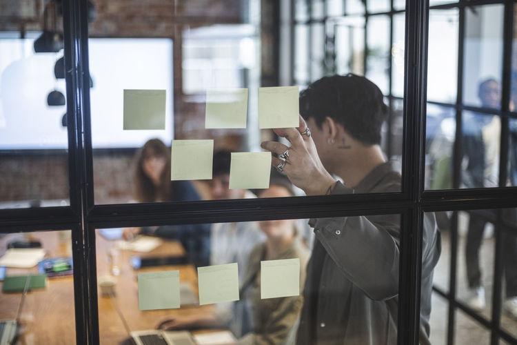 Portrait of people working in glass window