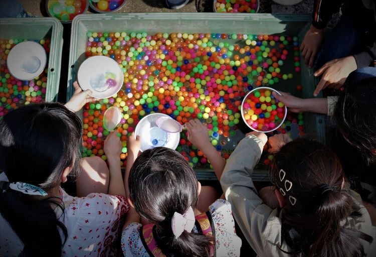 Directly Above Shot Of Girls With Colorful Balls Crate