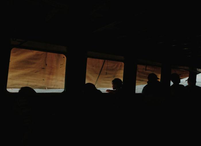 Silhouette people sitting in window