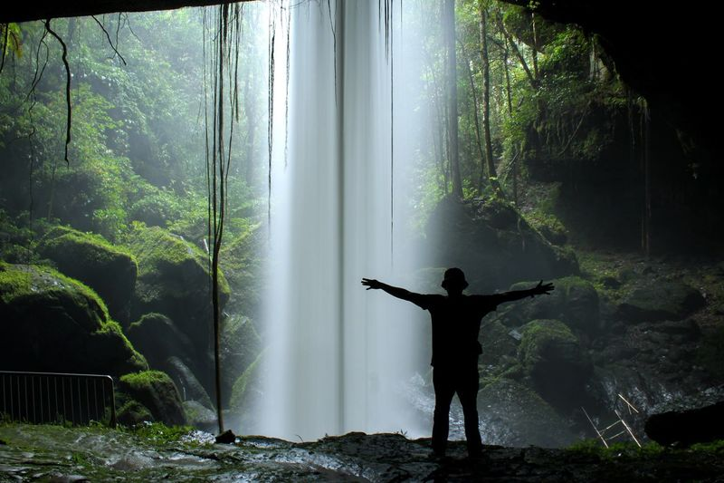 Silhouette of the man behind the waterfall