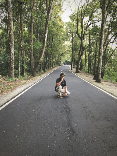 Full length of man crouching on road against trees