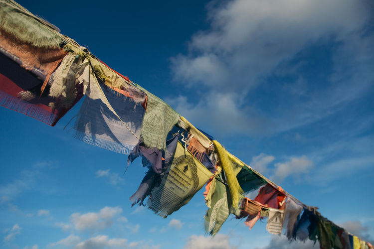 Low angle view of prayer flags hanging against sky