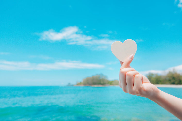 Midsection of person holding heart shape in sea against sky