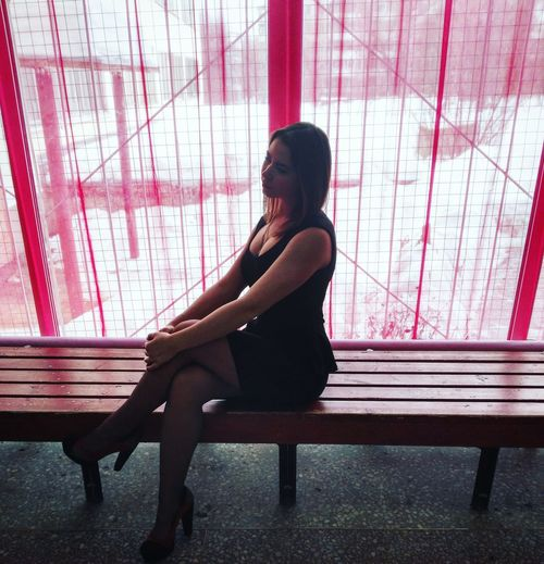 Sensuous woman sitting on wooden bench against red window during winter