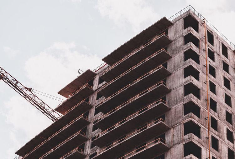 Skyscraper and building crane at a construction site.