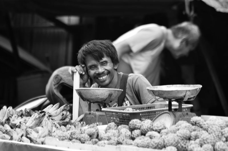 Smiling Mature Vendor Looking Away By Fruit Stall