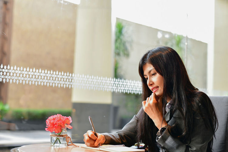 Adult Business Communication Contemplation Focus On Foreground Hair Hairstyle Holding Indoors  Leisure Activity Lifestyles Long Hair Looking One Person Real People Sitting Table Wireless Technology Women Young Adult Young Women
