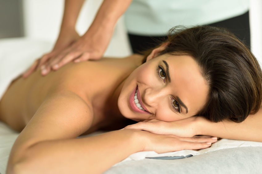 Young female receiving a relaxing back massage in a spa center. Brunette woman patient is receiving treatment by professional therapist. Center Happiness Happy Physio Relaxing Woman Beauty Face Lying Down Massage Massage Therapy Massages Physiotheraphy Physiotherapy Relax Smile Smiling Spa Therapist Treatment