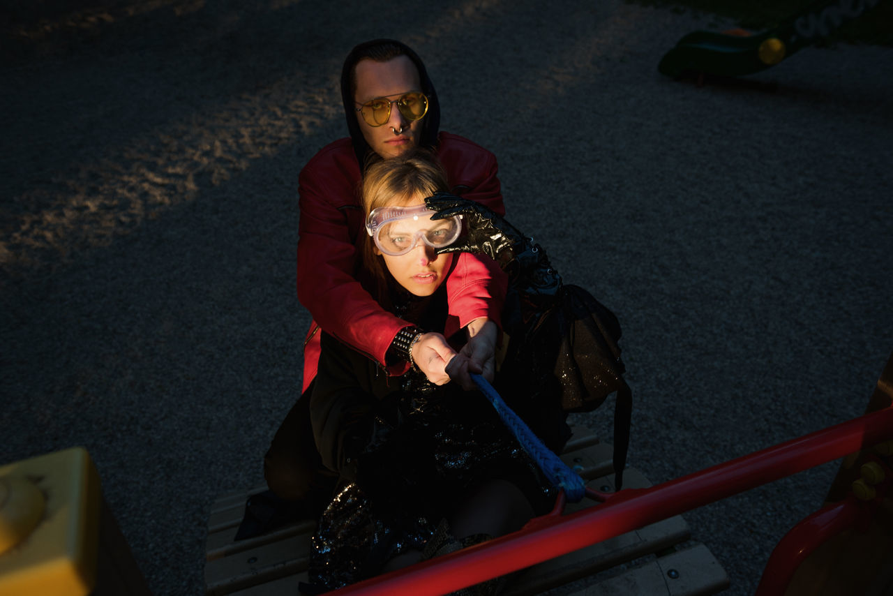 High angle portrait of couple on outdoor play equipment in playground at sunset