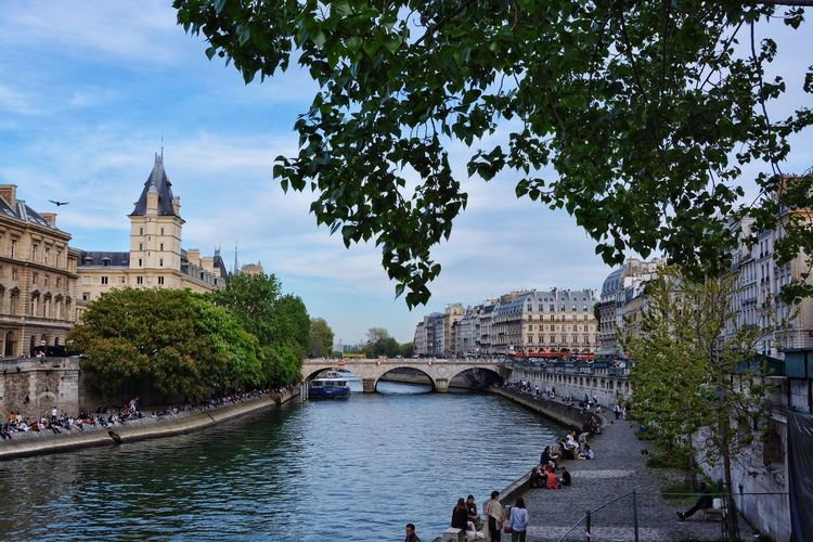 People on pier by seine river in city against sky