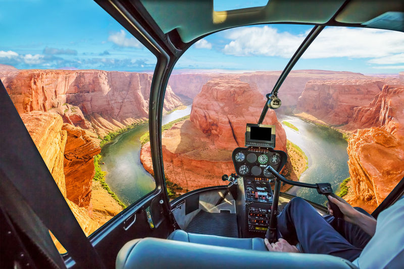 Helicopter cockpit scenic flight over Horseshoe Bend of Colorado River in Arizona, United States. Downstream from the Glen Canyon Dam and Lake Powell at sunset. United States Horseshoe Bend Horseshoe Bend, Utah Utah Sunset Colorado Colorado River Canyon USA America Aerial View Panorama Helycopter Flying Flight Mode Of Transportation Vehicle Interior Transportation Sky Landscape Day Nature One Person Glass - Material Cockpit Mountain Environment Windshield Scenics - Nature Cloud - Sky Air Vehicle Transparent Car Outdoors Real People