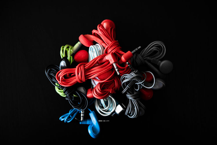 Directly above close up of heap of earphones multicolored Studio Shot Black Background Indoors  Still Life Close-up Red No People Multi Colored Copy Space Design Craft Pattern Representation Choice Large Group Of Objects Toy Earphones Audio Equipment Heap Stack