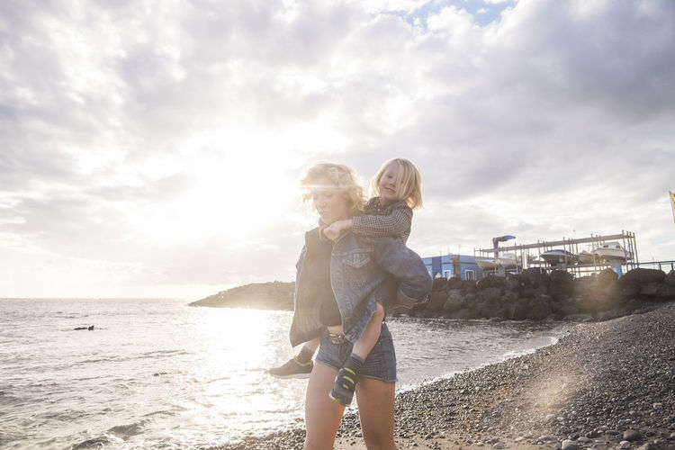Mother Piggybacking Cute Son While Walking At Beach Against Cloudy Sky During Sunset
