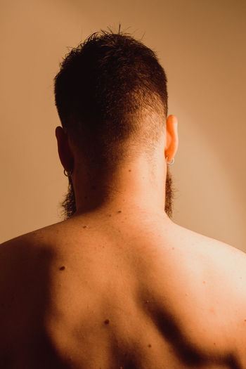 Rear view of shirtless man against gray background
