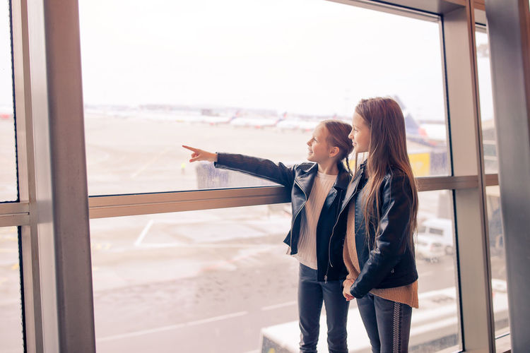 Smiling girls standing at airport