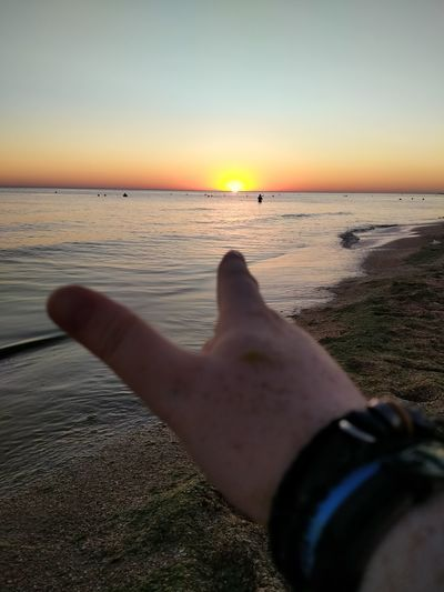 Midsection of person at sea shore against sky during sunset