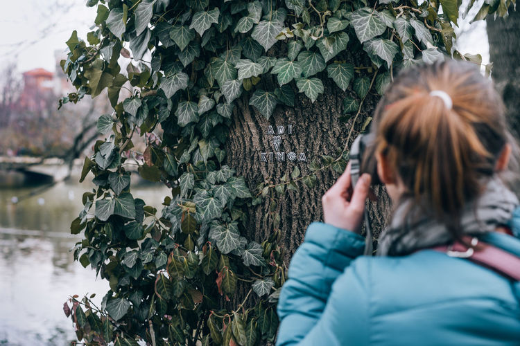 Close-up of woman photographing tree