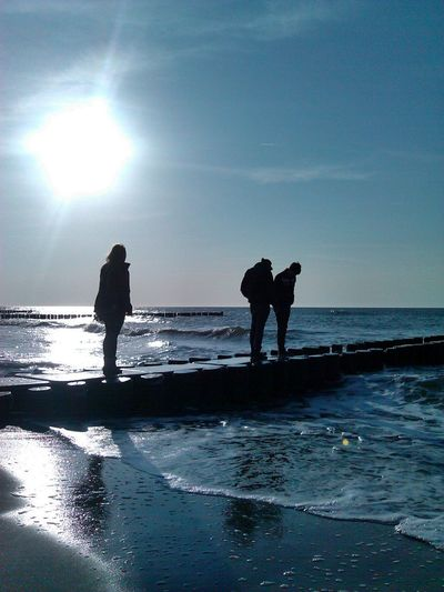 Full Length Of Silhouette Friends Standing On Broken Pier At Beach