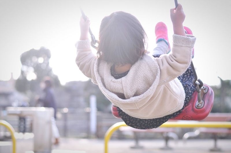 Rear view of girl swinging in park against sky