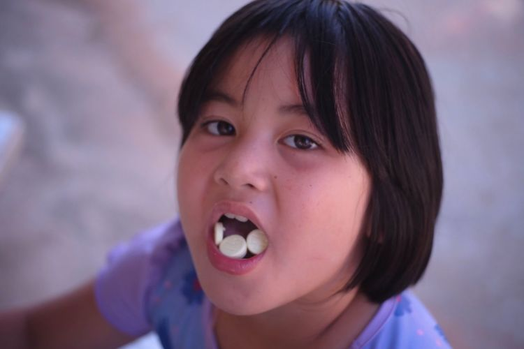 Close-up portrait of cute girl eating candy
