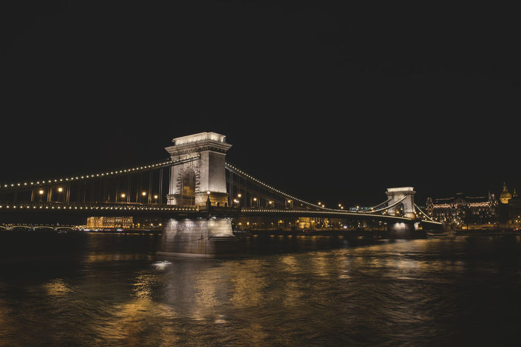 The Chain Bridge in Budapest that expans the Danube at night lights with city of Pest Background Architecture Bridge Bridge - Man Made Structure Built Structure Chain Bridge Connection Engineering Illuminated Night Reflection River Sky Suspension Bridge Transportation Travel Travel Destinations Water Waterfront