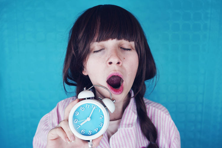 Close-up of young woman yawning with alarm clock against colored background
