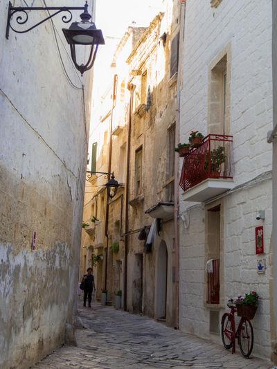 People walking on narrow street amidst buildings in city