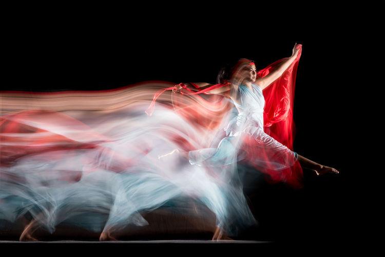 Digital composite image of women dancing against black background