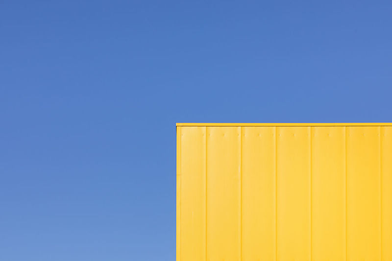 Low angle view of yellow cargo container against sky